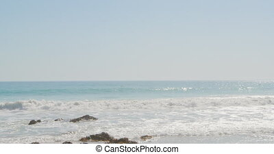 Sea and blue sky - View of an empty beach with waves ...