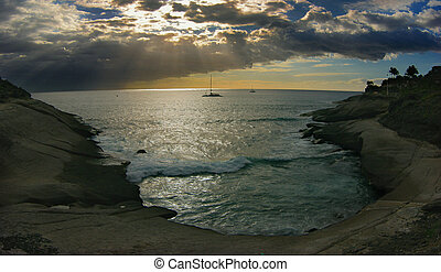 sunset on the ocean with clouds and boat