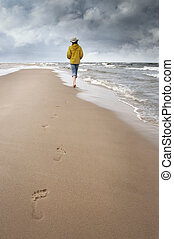 sea and lowering clouds - woman walks along coast and see on...