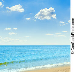 sea and sandy beach under a blue sky with clouds