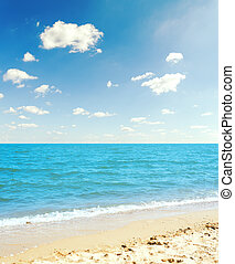 sea and yellow sand under blue sky with clouds
