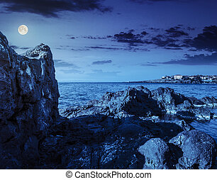 sea bay with boulders and old city at night - sea coast with...
