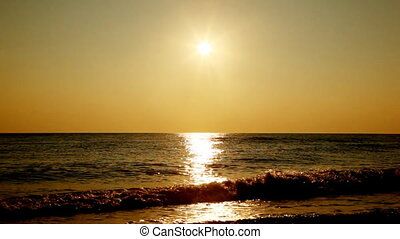 Sea, beach and evening sunset with its reflection in water