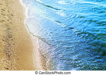 sea beach with sand and water line with sun reflection