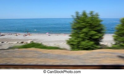 sea beach with tourists, view from window of moving train