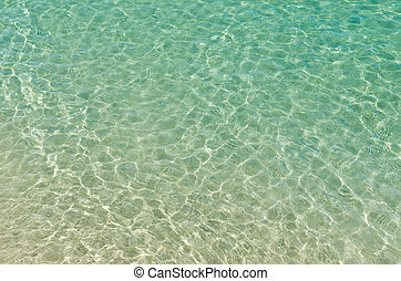 clear beach ripple water reflecting in the sun