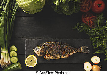 Sea bream cooked and ready to eat. Green vegetables around the fish
