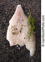 sea bream fillet with spice mix on a dark marble surface - ...