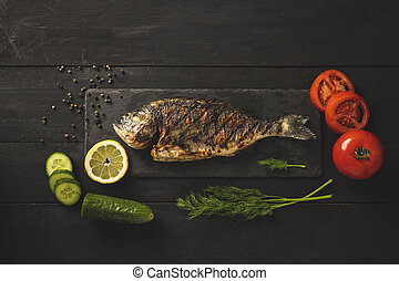 Sea bream fish with tomatoes, cucumbers, dill and a slice of lemon
