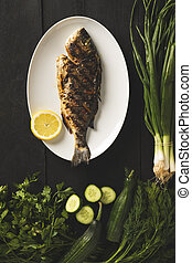 Sea bream on a white plate with green vegetables
