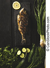 Sea bream or dorado fish with green fresh vegetables