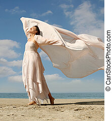 Beautiful woman with a scarf standing on the beach