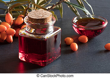 Sea buckthorn oil in a glass bottle with sea buckthorn branches