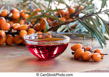Sea buckthorn oil in a glass bowl with sea buckthorn branches