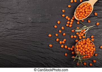 Sea buckthorn. Ripe fresh berries in bowl on black stone background with copy space for your text. Top view
