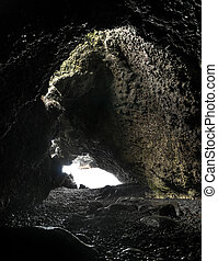 Sea Cave - Empty sea cave with black rocks and light coming...