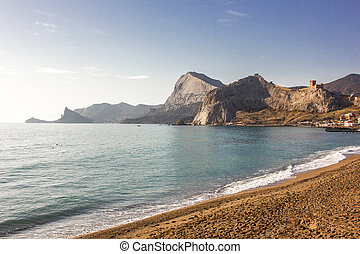 Sea coast and sandy beach with rocky mountains on a clear day