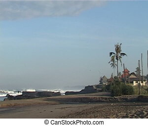 Sea coast in Bali with huge stones, palm and huts on sandy...