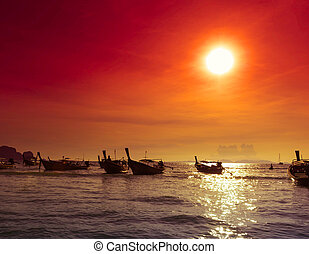 Sea coast landscape nature background, fishing boats silhouettes at evening  Red sunset with warm sun rays and dark ocean water in Asia