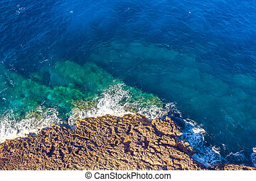 Sea coast on rocky beaches with turquoise water waves, aerial view.
