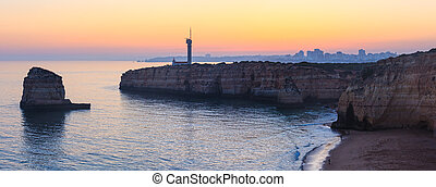 Sea coast sunset landscape and lighthouse.