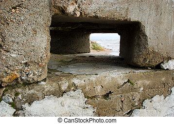 Sea coastline landscape through a window in a stone structure
