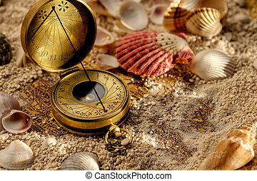 Ancient compass on the sand with seashells