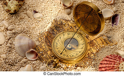 Ancient compass on the sand with seashells - Sea concept....