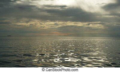 sea dramatic landscape at sunset rays through a cloudy dark sky,  first person view