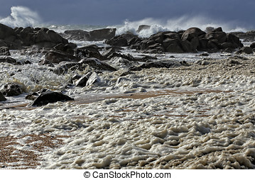 Sea foam in an empty seaside from the north of Portugal with...
