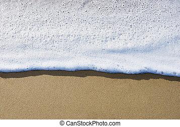 Sea foam - Sea wave moving over wet send making a foam.