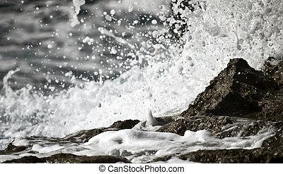 Sea Foam - Detail of ocean waters splashing on to a rocky...