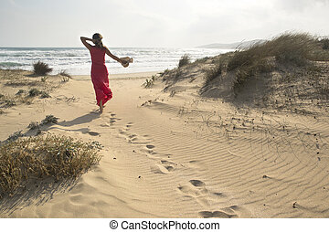 Sea freedom - A beautiful woman walks through sand dunes ...
