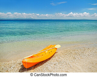 Sea kayak with a paddle on the beach
