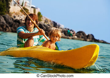Sea kayaking with children - Father with little son rowing...