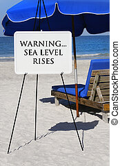 Sea Level Rises Warning - Sign at the ocean warning of the...