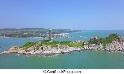 Sea light house on rocky island in blue sea and modern city on skyline, panoramic view from drone. Aerial view lighthouse tower on green island in ocean.