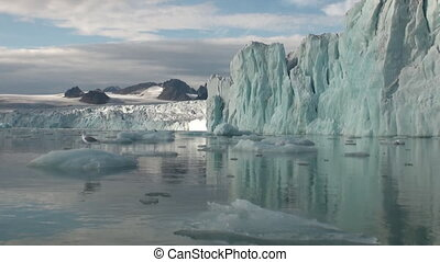 Sea mountains and large icebergs reflecting in the water. Fantastic wonderful amazing video grennlandii nature iceland. Lovely shooting the life of nature, seaside and mountains.