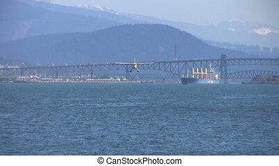 Sea Plane Landing In Harbor - A float plane flies over...
