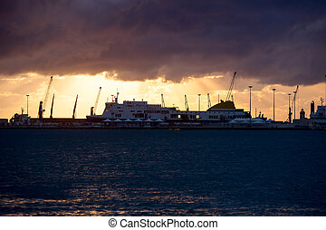 Sea port with big ships and lighthouse at sunset