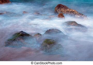 Sea rocks in haze at sunset