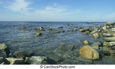 Sea rocky shore with clear blue water in the distance gulls...