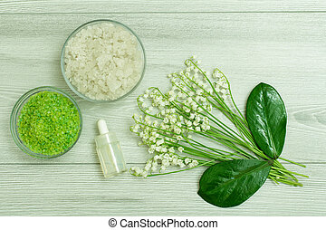 Sea salt, bottle with aromatic oil, green leaves and lilies of the valley
