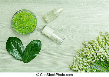 Sea salt, bottles with aromatic oil, green leaves and lilies of the valley