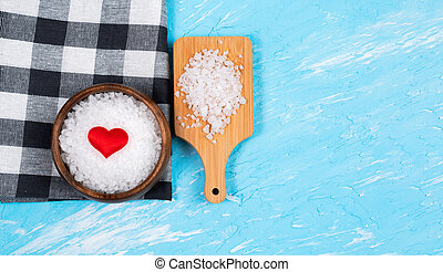 sea salt for food love heart on blue background with space to copy text