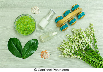Sea salt, green leaves and flowers, bottles with cream for face skin and oil