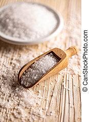 Sea salt in wooden shovel on wooden board