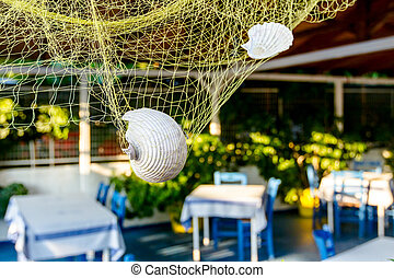 Sea shells with fishing net as artistic design in a typical outdoor Greek tavern