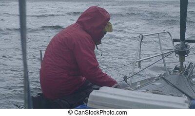 Sea ship mooring to barrel floating in water. Sailor man...