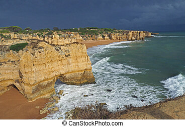 sea shore with beautiful beach rocks and sandstone cliffs and dramatic sky